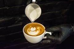 Cappuccinoschale mit Lattekunst Prozess der Vorbereitung des Kaffees mit Milch Arbeit barista Neues Getränk mit Koffein stockfotos