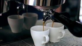 Cappuccinot hälls in i två rånar från kaffemaskinen arkivfilmer