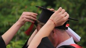 Cappuccio accademico d'uso laureato del maschio felice e sorridere, graduation video d archivio