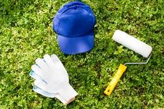 Cappuccio blu, rullo di pittura e guanti di lavoro bianchi su erba verde Fotografia Stock