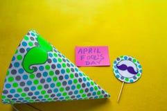 Cappuccio, cappello a cilindro con i baffi e note con il giorno del ` s del pesce d'aprile di frase su un fondo giallo Fotografia Stock
