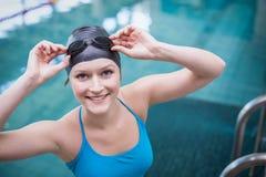 Cappuccio d'uso di nuotata della donna graziosa ed occhiali di protezione di nuoto Immagini Stock