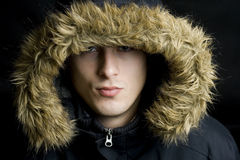 Cappuccio da portare della pelliccia del giovane uomo bello in inverno Fotografia Stock