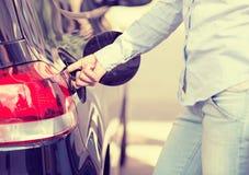 Cappuccio del carro armato di gas dell'automobile di apertura della donna alla stazione di servizio Immagini Stock