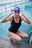 Cappuccio della donna graziosa occhiali di protezione accovacciantesi e d'usi di nuotata e Fotografia Stock Libera da Diritti