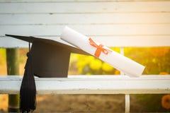 Cappuccio di graduazione, cappello con la carta di grado sulla tavola di legno bianca, sommario Immagine Stock