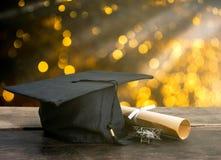 cappuccio di graduazione, cappello con la carta di grado sulla tavola di legno, Li astratto fotografie stock