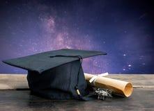 cappuccio di graduazione, cappello con la carta di grado sulla tavola di legno, Via Lattea b Fotografia Stock Libera da Diritti