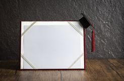 Cappuccio di graduazione sul concetto di istruzione del certificato di graduazione su di legno con fondo scuro immagine stock libera da diritti