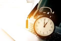 Cappuccio di graduazione sul retro orologio superiore del alam sul computer Concetto della a Immagine Stock