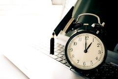 Cappuccio di graduazione sul retro orologio superiore del alam sul computer Concetto della a Fotografie Stock