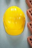 Cappuccio di sicurezza dei mattoni rossi sulla costruzione di vista superiore della superficie di calcestruzzo Fotografia Stock