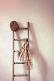 Cappuccio piano & sciarpa sulla scala rustica Immagine Stock