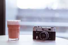 Cappucciono rosa del caff? dei pantaloni a vita bassa sulla tavola bianca con la retro macchina fotografica antiquata della foto  fotografia stock
