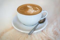 Cappuchino或拿铁coffe在一个白色杯子在轻的背景 图库摄影