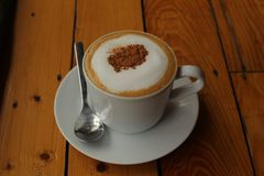 Cappuchino coffee in white porcellan cup and saucer with spoon. And cinnamon close up photo on wooden table Royalty Free Stock Images