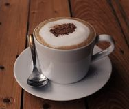 Cappuchino coffee in white porcellan cup and saucer with spoon. And cinnamon close up photo on wooden table Stock Photo