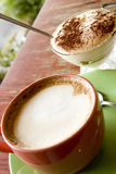 Cappuchino and dessert. The cup of coffee and cup of dessert Royalty Free Stock Images