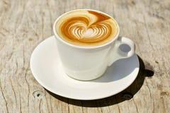 Cappuchino eller lattecoffe i en vit kopp med Royaltyfri Fotografi
