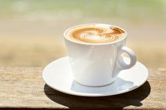 Cappuchino eller lattecoffe i en vit kopp med Royaltyfria Bilder