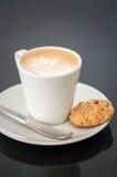 Cappuchino eller lattecoffe i en vit kopp och ett kex på en mörk bakgrund Royaltyfri Fotografi