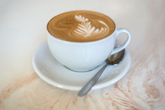 Cappuchino eller lattecoffe i en vit kopp på en ljus bakgrund Arkivbild