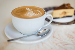 Cappuchino eller lattecoffe i en vit kopp på med en kaka Arkivfoto