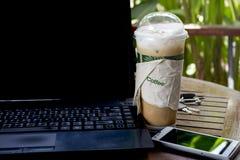 Cappuchino helado en la tabla con el teléfono y el cuaderno elegantes Imágenes de archivo libres de regalías