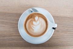Cappuchino-Kaffee in der weißen porcellan Schale und im silbernen Löffel Minimale Zusammensetzung, Hippie-Schwingungen Draufsicht stockfotografie