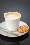Cappuchino or latte coffe in a white cup and a biscuit on a dark background Royalty Free Stock Photography