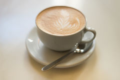 Cappuchino or latte coffe in a white cup on a light background Royalty Free Stock Photo