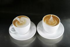 Cappucinno with Latte Art. Two single cappuccino's sitting ready with latte art Royalty Free Stock Image