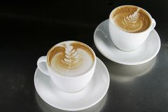 Cappucinno with Latte Art. Two single cappuccino's sitting ready with latte art Royalty Free Stock Photography