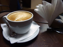 Cappucino cup. White cappucino cup with spoon on dark wood table Royalty Free Stock Photos