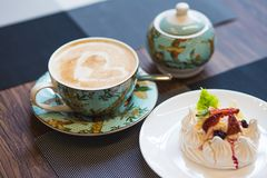 Cappucino do copo com arte do café do coração uma luz e uma sobremesa dos pavlova pairosos com merengue e fruto imagem de stock royalty free