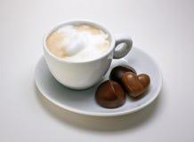 Cappucino en una placa con los chocolates Foto de archivo libre de regalías