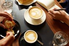 Cappucino, kawa espresso, ciasto i ręka bierze notatki, Fotografia Royalty Free