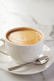 Cappucino or latte milk coffee in white cup and saucer in a cafe Royalty Free Stock Image
