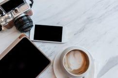 Cappucino, tableta, teléfono y cámara en una tabla blanca Imagenes de archivo
