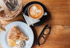 Cappucino, tarte de pomme, eyelgass et un panier de l'assaisonnement sur W Photos libres de droits