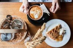Cappucino, tarte de pomme, poaceae et un panier de l'assaisonnement sur un OE Photographie stock