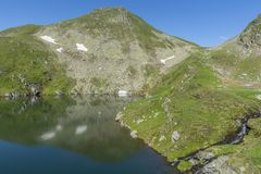 Beautiful view of high mountain lake. Landscape from Capra Lake in Romania and Fagaras mountains in the summer. royalty free stock photos