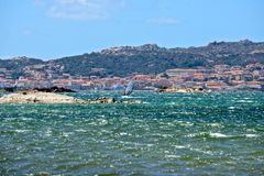 Caprera seascape with a man windsurfing. And the view of La Maddalena city in the background Stock Photos