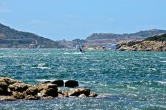 Caprera seascape with a man windsurfing. And the view of La Maddalena city in the background Stock Images