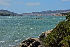 Caprera seascape with sea, plants, rocks. And the view of La Maddalena city Stock Images