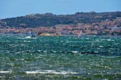 Caprera seascape with two men windsurfing. And the view of La Maddalena city in the background Royalty Free Stock Photo