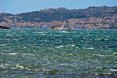 Caprera seascape with two men windsurfing. And the view of La Maddalena city in the background Royalty Free Stock Photos