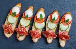 Caprese三明治用蕃茄,无盐干酪乳酪,蓬蒿,在ciabatta面包的蒜味咸腊肠在石板岩背景关闭 免版税库存图片