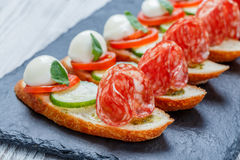 Caprese三明治用蕃茄,无盐干酪乳酪,蓬蒿,在ciabatta面包的蒜味咸腊肠在石板岩背景关闭 免版税库存照片