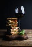 Caprese三明治或panini和杯红葡萄酒 整个五谷面包,无盐干酪,烘干了蕃茄,蓬蒿 可能 免版税库存图片
